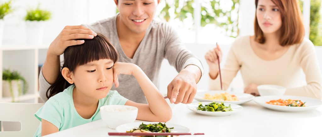 parent coaxing child to eat vegetables child not happy